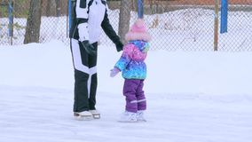 A mamã ensina sua filha pequena patinar na pista vídeos de arquivo