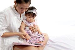 A mamã está jogando a tabuleta com seu bebê Fotografia de Stock