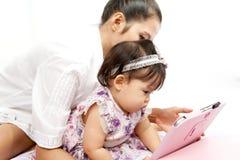 A mamã está jogando a tabuleta com seu bebê Imagens de Stock Royalty Free