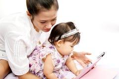 A mamã está jogando a tabuleta com seu bebê Fotos de Stock Royalty Free
