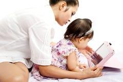 A mamã está jogando a tabuleta com seu bebê Foto de Stock