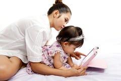 A mamã está jogando a tabuleta com seu bebê Imagens de Stock