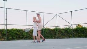 A mamã está tentando ensinar para jogar o tênis Atividades da fam?lia video estoque