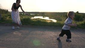 A mamã faz bolhas e o menino corre ao longo da estrada, morde-as, movimento lento video estoque