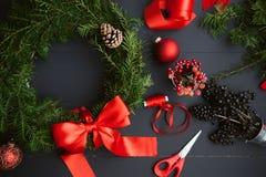 A mamã faz uma grinalda do Natal com suas próprias mãos Fotos de Stock