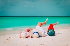 A mamã feliz com filho e a filha relaxam na praia foto de stock