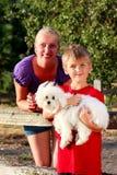 Mamã feliz com sua criança e um cão de estimação Imagem de Stock Royalty Free