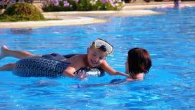Mamã feliz da família e filho pequeno em uma nadada do círculo na associação com água azul no hotel Movimento lento filme