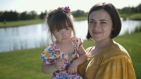 Mamã feliz e filha que levantam na câmera no parque filme