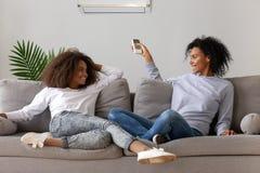Mamã feliz e filha que relaxam no sofá sob o condicionador de ar imagens de stock royalty free