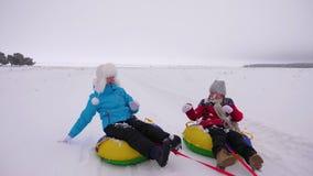 Mamã feliz e filha que sledding no inverno na neve e que jogam bolas de neve riso da mãe e da criança e para exultar o deslize no filme