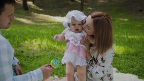 Mamã feliz e paizinho da família que jogam com o bebê na colcha filme