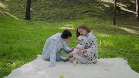 Mamã feliz e paizinho da família que jogam com o bebê na colcha video estoque