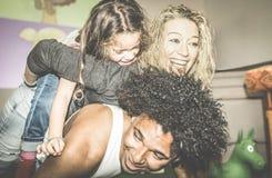 Mamã feliz e paizinho multirraciais que jogam com a filha da raça misturada imagem de stock