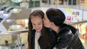 A mamã feliz em um casaco de cabedal abraça sua filha em um grande shopping filme