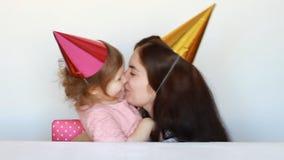 A mamã feliz felicita a criança na festa de anos Sira de mãe e seu abraço da filha, beije e expresse o amor filme