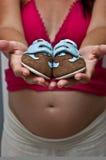Mamã grávida que mostra duas sapatas de bebê Fotografia de Stock Royalty Free