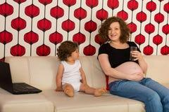 Mamã grávida que tem a conversação com filho imagens de stock