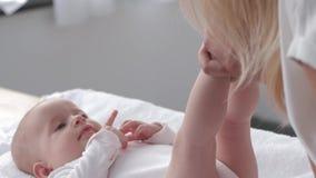 A mamã guarda os pés pequenos da filha então delicadamente toca e beija- n, bebê feliz que encontra-se na tabela em mudança