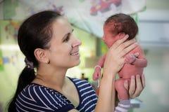 A mamã guarda um bebê recém-nascido Fotografia de Stock Royalty Free