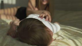 Mamã loura nova bonita que joga com seu filho do bebê - objetivo dos valores familiares - mãe e criança caucasianos em casa - vídeos de arquivo