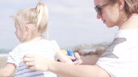 A mamã mancha a cara da proteção pequena do creme da filha do sol vídeos de arquivo