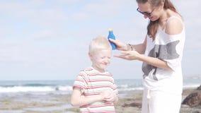 A mamã mancha seu filho louro para proteger contra a queimadura video estoque
