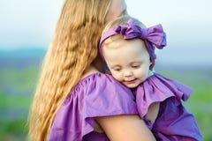 A mamã mantém a filha em seus braços e jogos na natureza Mãe bonita e feliz com sua menina que joga fora imagem de stock
