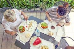 Mamã moderna e filha nova que comem o almoço Imagem de Stock