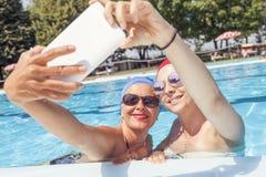 A mamã moderna e a filha nova tomam um selfie Fotografia de Stock