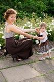 A mamã mostra as flores da criança foto de stock