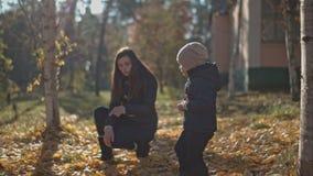 A mamã mostra até seu filho no parque do outono video estoque