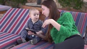 A mamã mostra o vídeo no telefone ao bebê e ensina-o dançar no movimento lento video estoque