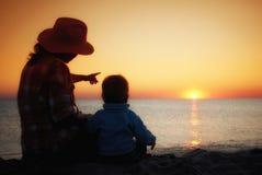 A mamã mostra seu por do sol novo do filho no mar Foto de Stock