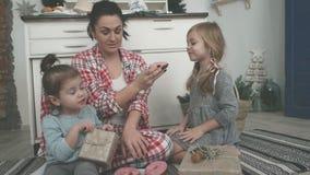 A mamã nova bonita e sua filha pequena bonito estão jogando com cortadores da cookie e estão sorrindo ao cozer na cozinha em filme