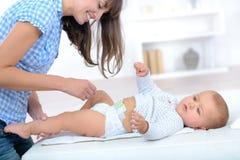 Mamã nova bonita que muda fraldas pequenas encantadores do bebê Fotografia de Stock