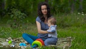 Mamã nova com jogo pequeno do bebê no jardim filme