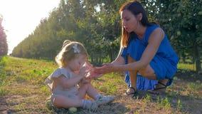 A mamã nova dá o vidro da água à criança bonito que senta-se na grama entre fileiras das árvores fora durante a estação da colhei video estoque