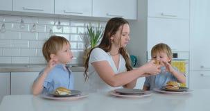 Mamã nova da família e dois filhos que sentam-se na cozinha na tabela branca que come hamburgueres junto e que tem o divertimen video estoque