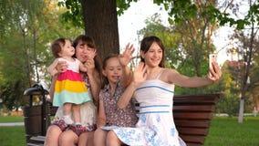 Mamã nova das crianças felizes que estão sendo fotografadas no smartphone uma família feliz que senta-se no banco em fazer do par filme