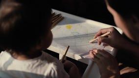 A mamã nova feliz tira um lápis com seu bebê bonito pequeno no papel filme