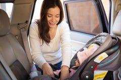 Mamã nova que fixa um banco de carro da criança foto de stock
