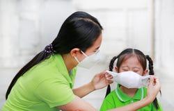 Mamã nova que veste a máscara protetora para sua filha quando parte externa contra a PM 2 polui??o do ar 5 na cidade de Banguecoq fotografia de stock