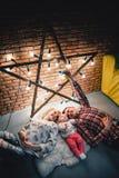 a mamã, o paizinho e o bebê encontram-se em um tapete e em um sorriso de lã foto de stock royalty free
