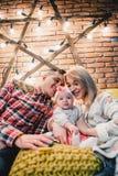 a mamã, o paizinho e o bebê sentam-se no sofá e no abraço imagens de stock