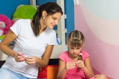 A mamã olha enquanto a filha faz ofícios imagem de stock