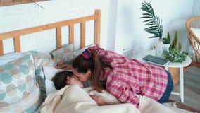 A mamã põe filhas para colocar, beija-as, deseja a boa noite, movimento lento