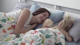 A mamã põe sua filha pequena para dormir em uma sesta vídeos de arquivo