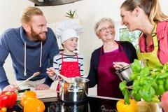 Mamã, paizinho, avó e neto junto na cozinha que prepara o alimento foto de stock