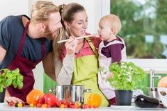 Mamã, paizinho e criança na cozinha imagem de stock royalty free